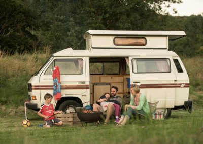 Family sitting outside their camper van
